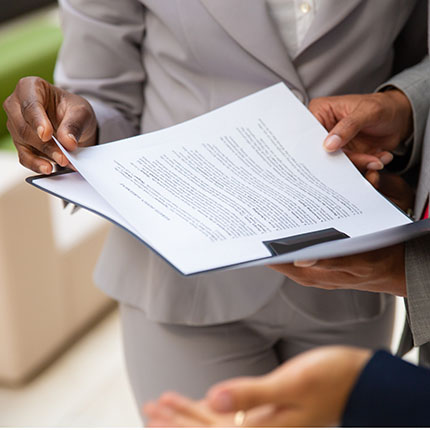 Diverse business partners reading contract together. Business man and woman wearing formal suits, standing and holding open folder with document. Agreement concept